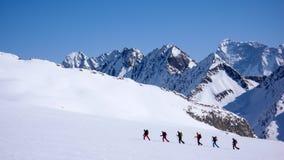 Grupo de esquiadores backcountry que cruzam uma geleira em sua maneira a uma cimeira alta nos cumes Imagens de Stock