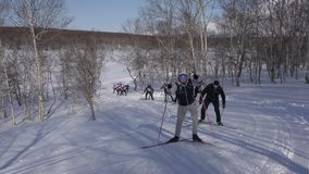 Grupo de esquiadores que corren a lo largo de pista del esquí en bosque del invierno almacen de metraje de vídeo