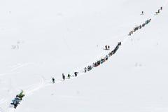 Grupo de esquiadores y de snowboarders que suben la montaña para el freeride Foto de archivo