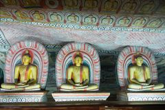 Grupo de estátuas de assento da Buda no templo budista da caverna Imagens de Stock