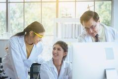Grupo de estudante de Medicina asiática que trabalha e que analisa a informação da pesquisa dos dados junto no laboratary imagem de stock royalty free