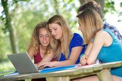 Grupo de estudante novo que usa o portátil ao ar livre foto de stock