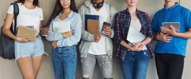 Grupo de estudantes com livros, dispositivos e trouxas imagens de stock royalty free