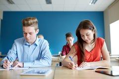 Grupo de estudantes com livros que escrevem o teste da escola foto de stock