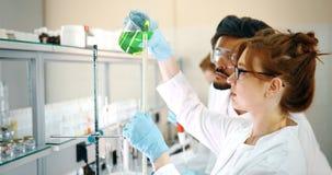Grupo de estudantes da química que trabalham no laboratório foto de stock