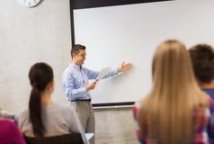 Grupo de estudantes e de professor de sorriso com bloco de notas Imagens de Stock Royalty Free