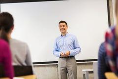 Grupo de estudantes e de professor de sorriso na sala de aula imagens de stock