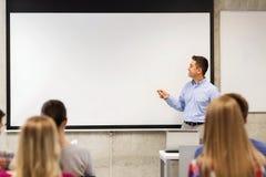 Grupo de estudantes e de professor de sorriso na sala de aula Fotos de Stock Royalty Free