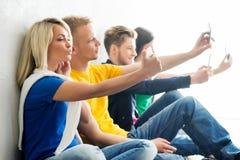 Grupo de estudantes felizes que estão em uma ruptura que toma o selfie imagens de stock royalty free