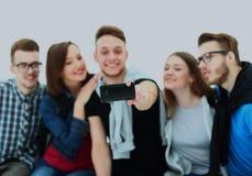 Grupo de estudantes novos felizes do adolescente que tomam a foto do selfie isolada no fundo branco Fotografia de Stock