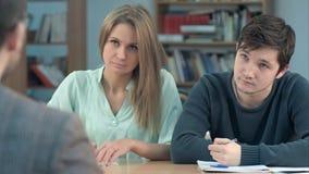 Grupo de estudantes novos que escrevem algo em suas almofadas de nota ao sentar-se em seguido em suas mesas Imagem de Stock