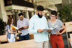 Grupo de estudantes novos que estudam junto na biblioteca Imagens de Stock Royalty Free