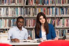 Grupo de estudantes novos que sentam-se na biblioteca imagens de stock royalty free