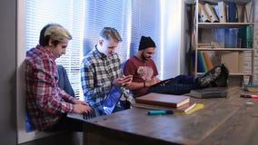 Grupo de estudantes que estudam usando dispositivos digitais video estoque