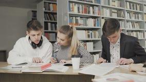 Grupo de estudantes que preparam-se para o exame na biblioteca da universidade filme