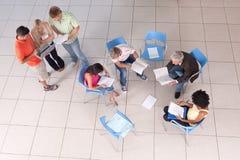 Grupo de estudantes que sentam-se para baixo com conferente Fotografia de Stock Royalty Free
