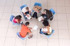 Grupo de estudantes que sentam-se para baixo com conferente Imagens de Stock