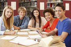 Grupo de estudantes que trabalham junto na biblioteca Imagens de Stock