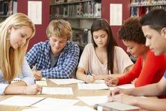 Grupo de estudantes que trabalham junto na biblioteca Fotografia de Stock