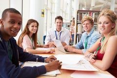 Grupo de estudantes que trabalham junto na biblioteca com professor Foto de Stock Royalty Free