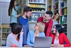 Grupo de estudantes que trabalham junto na biblioteca com professor Fotografia de Stock