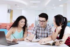 Grupo de estudantes universitário que estudam na biblioteca fotografia de stock royalty free