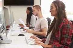 Grupo de estudantes universitário que usam recursos em linha imagem de stock