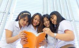 Grupo de estudantes universitários que lêem junto Fotos de Stock Royalty Free