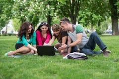Grupo de estudiante joven que usa el ordenador portátil junto Fotos de archivo libres de regalías