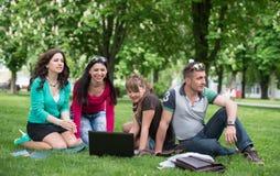 Grupo de estudiante joven que usa el ordenador portátil junto Fotografía de archivo