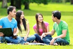 Grupo de estudiante joven que usa la computadora portátil al aire libre Foto de archivo libre de regalías