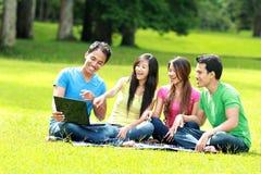 Grupo de estudiante joven que usa la computadora portátil al aire libre Imagenes de archivo
