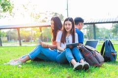 Grupo de estudiante universitario asiático que usa la tableta y el ordenador portátil en hierba Imagenes de archivo