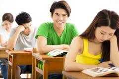 Grupo de estudiante universitario joven que se sienta en una sala de clase Imagen de archivo
