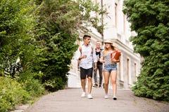 Grupo de estudiantes adolescentes atractivos que caminan de universidad imagenes de archivo