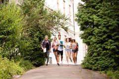 Grupo de estudiantes adolescentes atractivos que corren de universidad Fotos de archivo
