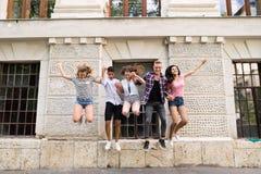 Grupo de estudiantes adolescentes delante de la universidad que salta arriba Imágenes de archivo libres de regalías