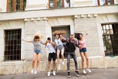 Grupo de estudiantes adolescentes delante de la universidad que salta arriba Fotografía de archivo
