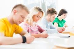 Grupo de estudiantes adolescentes en el examen en el auditorio Imágenes de archivo libres de regalías