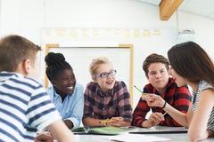 Grupo de estudiantes adolescentes que colaboran en proyecto en sala de clase fotos de archivo