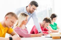 Grupo de estudiantes adolescentes que estudian en la lección en la sala de clase Fotos de archivo libres de regalías