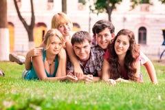 Grupo de estudiantes adolescentes sonrientes felices afuera Foto de archivo libre de regalías