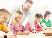 Grupo de estudiantes adolescentes y de un profesor en la lección en el cla Imagenes de archivo
