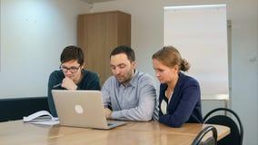 Grupo de estudiantes alegres positivos que usan el ordenador portátil y haciendo la preparación junta en sala de clase Fotos de archivo