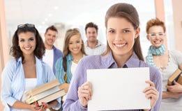 Grupo de estudiantes con la hoja en blanco para el copyspace Fotografía de archivo libre de regalías