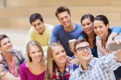 Grupo de estudiantes con la taza del smartphone y de café Fotos de archivo libres de regalías