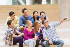 Grupo de estudiantes con la taza del smartphone y de café Fotografía de archivo libre de regalías