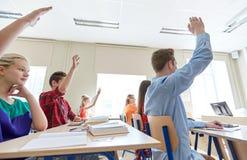 Grupo de estudiantes con las manos aumentadas en la High School secundaria Imágenes de archivo libres de regalías