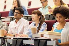 Grupo de estudiantes con los cuadernos en conferencia Imagen de archivo