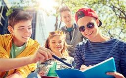 Grupo de estudiantes con los cuadernos en el patio de escuela Fotos de archivo